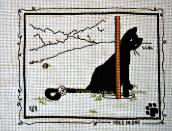 "Cross Stitch Embroidery picture of a cat and text saying ""Hole in One"" for framing"