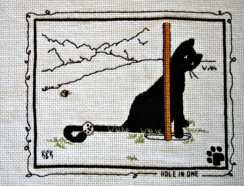 """Cross Stitch Embroidery picture of a cat and text saying """"Hole in One"""" for framing"""